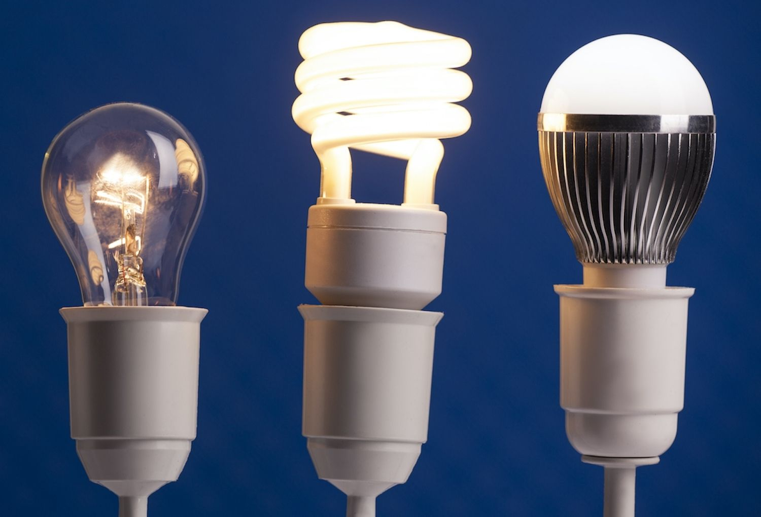 Three different light bulbs on blue background, choosing a new lightbulb gives opportunity for an electrical upgrade!