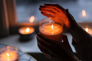 Person holding a light candle in the dark.