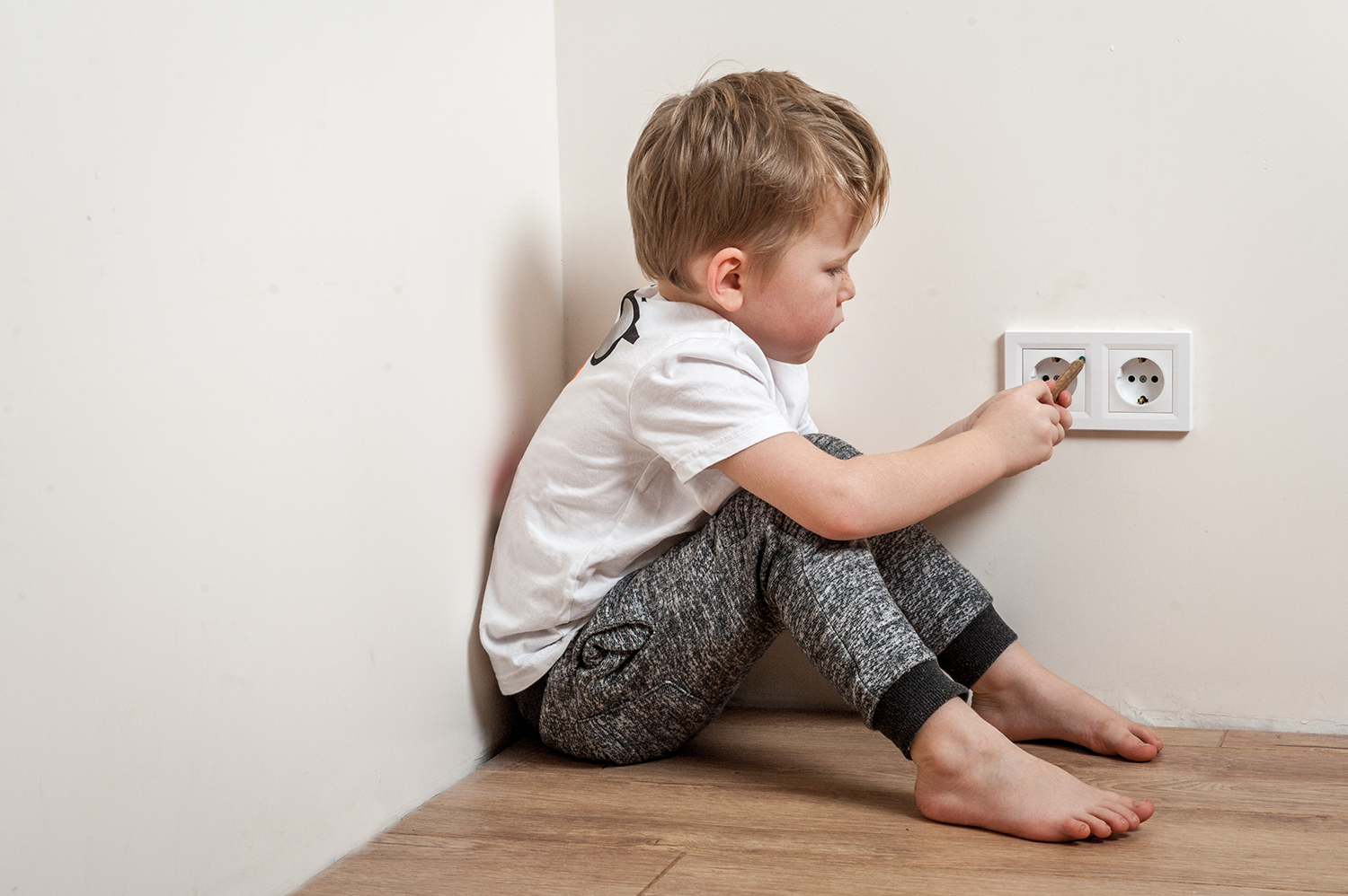 Kid sticking his finger in an outlet, a bad example of electrical safety.