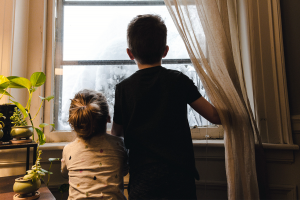 A little boy and little girl looking out a rainy window.