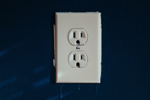 An electrical outlet on a blue wall, an important piece in electrical safety.
