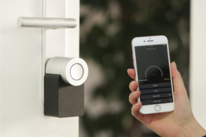 Smart home lock with person holding up phone with accompanying app.