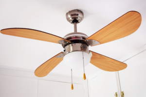Ceiling fan in a white room with wooden blades and light bulbs that keep burning out.